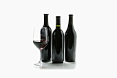 Glass of Red Wine with Three Wine Bottles