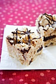 Two Rice Krispie Treats with Chocolate Drizzles on a Napkin