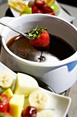 Strawberry Dipping into Chocolate Fondue