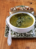 Bowl of Kale Soup with Slice of Whole Grain Bread