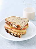 Peanut Butter and Apple Sandwich on Whole Grain Bread; Glass of Rice Milk