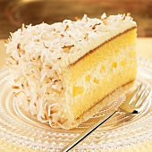 Slice of Pineapple Cream Cake with Toasted Coconut; Fork