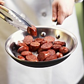 Hands Holding Tongs with a Piece of Andouille Sausage over Skillet
