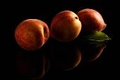 Drei Pfirsiche mit Reflexion