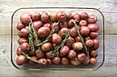 Red Potatoes and Rosemary Ready for Roasting in Glass Dish