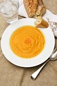 Bowl of Homemade Carrot Soup with Crusty Bread and Water