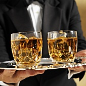 Waiter Serving Two Scotch on the Rocks on a Silver Platter