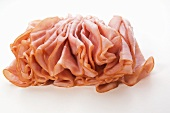 Thinly Sliced Ham on a White Background