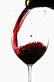 Red Wine Pouring into a Glass from Bottle; White Background