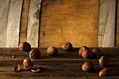 Whole Hazelnuts with One Cracked Open on Wood