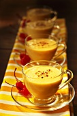Cups of Mango Lassi with Cinnamon and Cherries