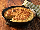 Cornbread in Cast Iron Skillet with Slice Removed