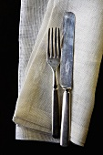 Old Fork and Knife on Linen Napkin