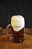 Glass Mug of Beer with Foam Overflowing