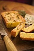 Partially Sliced Polenta Bread on Cutting Board; Knife