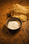 Coarse Salt in a Small Bowl on Wooden Table with Peppercorns and Parmesan Cheese