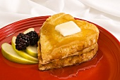Heart-shaped pancakes with butter and maple syrup, fresh fruit