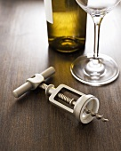 Corkscrew; Wine Glass and Bottle of White Wine on Wood