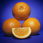 Orange Wedge In Front of Three Stacked Oranges