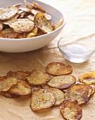 Homemade Potato Chips on Paper; Bowl of Salt