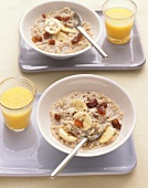 Bowl of Oatmeal with Dried Fruit and Banana; Glass of Orange Juice