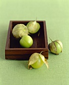 Fresh Tomatillos; In and Beside a Wooden Box