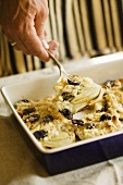 Scooping Baked Fennel with Blue Cheese, Olives and Bread Crumbs from Baking Dish