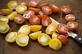Fresh Yellow and Red Cherry Tomatoes; Halved on Cutting Board with Knife