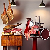 An arrangement of various raw hams and a sewing machine