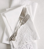 Antike Silbergabeln auf weissen Stoffservietten
