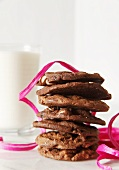 Stack of Chocolate Cookies with Pink Ribbon and Glass of Milk