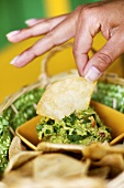 Hand Dipping Tortilla Chip into Guacamole
