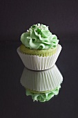 Green Cupcake with Green Frosting and Sprinkles; On Mirrored Surface