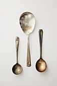 Three Antique Spoons on a White Background