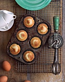 Cupcakes Still in Pan on Cooling Rack; Baking Tools and Ingredients