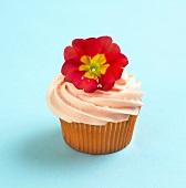 Cupcake with Orange Frosting and Red Primrose Garnish