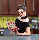 Frau mit Kochbuch im Stil der 50er Jahre in der Küche