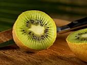 Halved Kiwi on Cutting Board; Knife