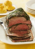 Herb Encrusted Roast Beef Partially Sliced on a Platter