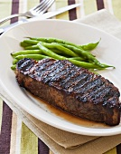 Grilled New York Strip Steak with Green Beans on White Plate