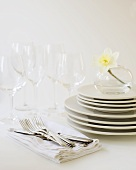 Stack of White Plates with White Napkins, Flatware and Glasses