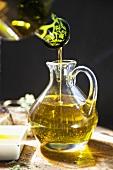 Kaltgepresstes Olivenöl in Glaskrug gießen