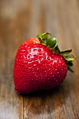 A strawberry on wooden background