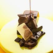 Geschmolzene Schokolade läuft über verschiedene Schokoladenstücke