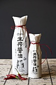 Two Bottles of Asian Sauce Wrapped in Paper Tied with Red String