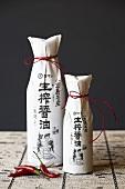 Zwei Flaschen mit asiatischer Sauce in Papier verpackt mit roter Schnur
