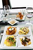 Four Assorted Pasta Dishes on Four Square White Plates; With Wine
