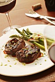 Two Filet Mignons on a Plate with Asparagus; Red Wine