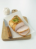 Partially Sliced Pork Roast on Cutting Board with Knife