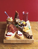 Appetizer Cheese Board with Cheese, Prosciutto, Bread and Olives